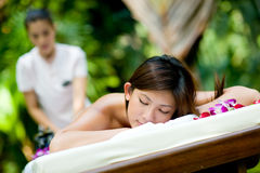 Outdoor Massage. A young woman having massage outside in tropical garden Royalty Free Stock Photos