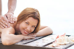 Outdoor massage. Young woman being massaged outdoor Stock Photos