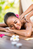 Outdoor massage. Young woman having massage outside in tropical garden Stock Images