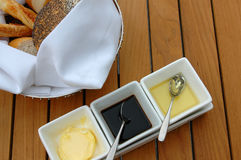 Outdoor meal. Basket of bread with butter, olive oil and vinegar Royalty Free Stock Photography