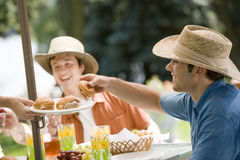 Outdoor meal with friends. Happy young friends having a picnic in the summer Royalty Free Stock Photography