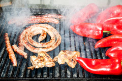 Outdoor meat BBQ with vegetables. Close-up of sausages and red bell peppers on the grill with smoke stock images