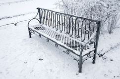 Outdoor metal bench covered with snow in winter Royalty Free Stock Photos