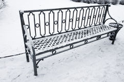Outdoor metal bench covered with snow in winter Stock Image