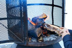 Outdoor metallic fireplace in winter season charged with firewood, in the burning process. Wood-burning fire pit with removable fire pan and with wide bar ribs stock photos
