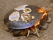 Outdoor middle east cooking. A metal round plate on firecamp for cooking pita Stock Images