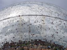 Outdoor mirror ball made of thousands of pieces of glass reflecting a grey cloudy sky and fragmented images of an urban street. An outdoor mirror ball made of stock photography