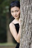 Outdoor Model 18. A beautiful asian woman peeks out from behind a tree in her black evening dress Stock Images