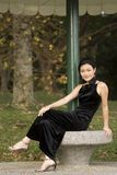 Outdoor Model 21. A beautiful young asian woman poses on a concrete bench in a black evening dress Royalty Free Stock Images
