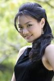 Outdoor Model 4. A beautiful demure asian model in a black evening dress posing outdoors Royalty Free Stock Image