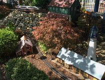 Outdoor model train track with train station lighthouse and barn Stock Photos