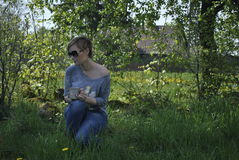 Young blond woman sitting in the garden in the sunny day royalty free stock images