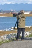 Outdoor Nature Photographer and Equipment. A nature photographer wearing camouflage clothing and equipment, stands by a waterway photographing wild birds Stock Photo