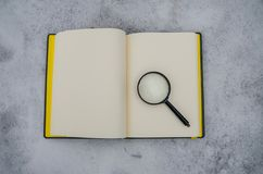 Open notebook and magnifying glass on the background of white snow royalty free stock photography