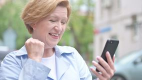 Outdoor Old Woman Excited for Success while Using Smartphone stock video footage