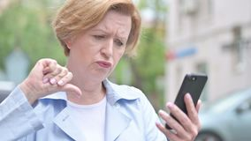 Outdoor Old Woman Reacting to Loss on Smartphone. 4k high quality, 4k high quality stock footage