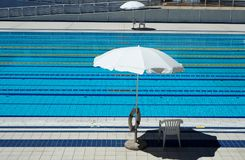Outdoor Olympic swimming pool with  lanes for races and 2 umbrellas per side for the lifeguards Royalty Free Stock Photography