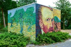 Vincent van Gogh Street Art painted on a brick wall. Outdoor painted brick wall with an art piece and self-portrait of Vincent van Gogh. Painted in green, blue stock photo