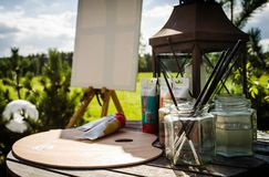Outdoor painting on easel. Acrylic paint, brushes royalty free stock photo