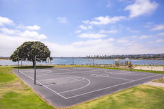 Outdoor park with black top and two basketball courts on the bay of San Diego California on a bright sunny day. Outdoors in Southern California homes ready for Royalty Free Stock Images