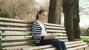 Outdoor park education. Leisure time. Young cute teen sitting bench reading book stock video footage