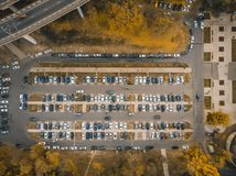 Outdoor parking lot or car park with rows of autos in urban landscape, aerial or top view. Toned royalty free stock photography