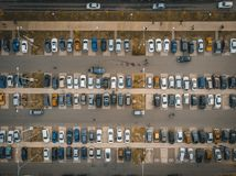 Outdoor parking lot or car park with rows of autos in urban landscape, aerial or top view. Toned royalty free stock images