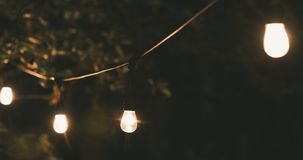 Outdoor party string lights hanging on a line in backyard. dolly shot. Outdoor party string lights hanging on a line in backyard. 4k dolly shot stock footage