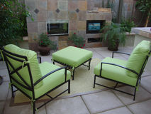 Outdoor Patio. Beautiful outdoor patio with two green chairs a foot stool a fireplace and a tv or television Royalty Free Stock Photos