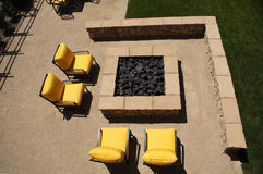 Outdoor Patio. Beautiful outdoor patio with four bright yellow chairs and a fire pit in the middle Stock Image