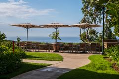 Patio with three tables with umbrellas. There is a stone wall. Patio overlooks the ocean royalty free stock photography