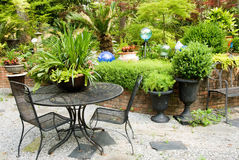Outdoor Patio Furniture in a Landscaped Flower Garden Stock Image