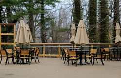 Outdoor patio with metal and wood table and chairs. Pretty woodsy setting, with metal tables and wood chairs, on outdoor patio of restaurant Stock Images
