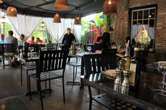 Outdoor patio with patrons enjoying a meal,Forno Bistro,Saratoga,NY,2015. Warm setting of table and chairs under cover in outdoor patio, where patrons enjoy a Stock Photos