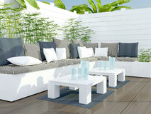 Outdoor patio seating area. Outdoor patio seating area with big white sofa and table Royalty Free Stock Images