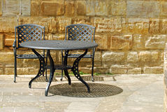 Outdoor patio set with rock wall. On a sunny day Royalty Free Stock Images