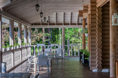 Outdoor patio with tables and vases, rustic house in forest Royalty Free Stock Photos