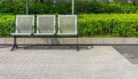 New modern metal seat with perforation. It is on outdoor pavement in garden Stock Images
