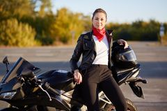 Outdoor photo of beautiful female driver sitting on black motobike, wears leather jacket, black trousers, white shirt and has red stock photography