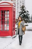 Outdoor photo of caucasian female model in gray coat and dark pants chilling in park with red call-box. Charming. Fashionable woman with smartphone enjoying royalty free stock photos