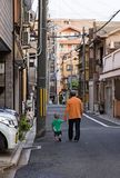 Outdoor photo of elderly man walking with young toddler on street in Kyoto, Japan. stock images