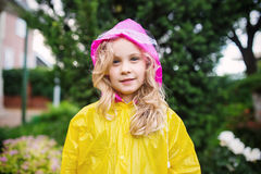 Outdoor photo of little blonde girl in yellow raincoat Royalty Free Stock Photo
