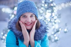 Outdoor photo of young beautiful female walks on street, wears stylish winter clothes, admires magic lights, has pleased expressio royalty free stock photo