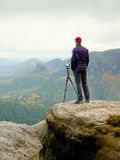 Outdoor photographer with tripod and camera on rock thinking. Autumnal valley. Outdoor photographer with tripod and camera on rock thinking. Creamy mist in Stock Images