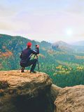Outdoor photographer with tripod and camera on rock thinking. Autumnal valley. Outdoor photographer with tripod and camera on rock thinking. Creamy mist in Royalty Free Stock Photography