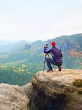 Outdoor photographer with tripod and camera on rock thinking. Autumnal valley. Outdoor photographer with tripod and camera on rock thinking. Creamy mist in Stock Photo