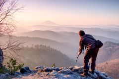 Outdoor photographer with the tripod and camera on rock thinking. Thick fog in autumnal countryside. Man work on sharp clif royalty free stock images