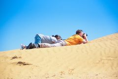 Outdoor photographers lie on sand dune taking pictures royalty free stock photos