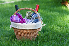 Outdoor picnic basket with wine on lawn Stock Photos