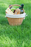 Outdoor picnic basket with wine on lawn Stock Photo